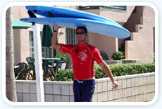 Man carrying surfboard over head