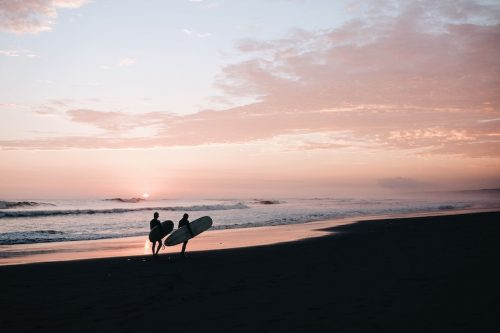 #1 Male and female surfer walking along beach after session